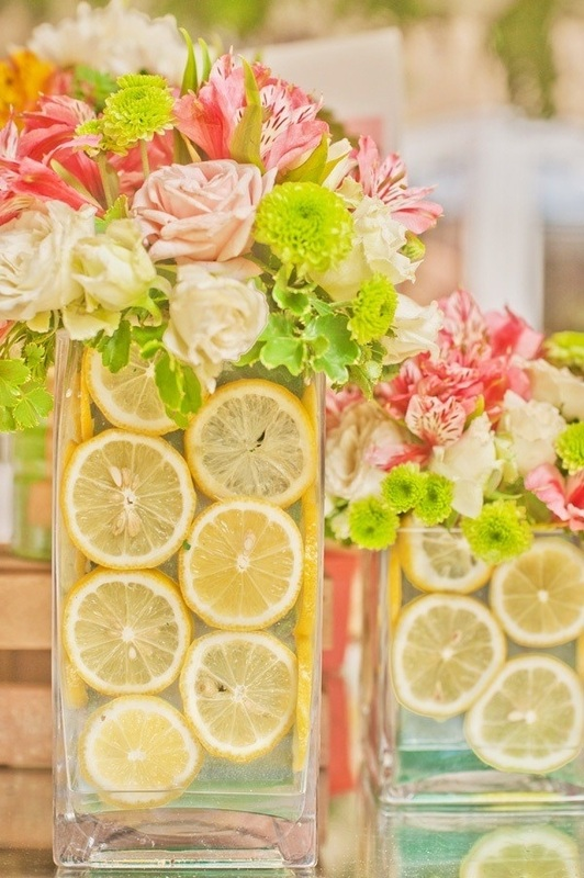 pink and green flowers in vases with lemon slices