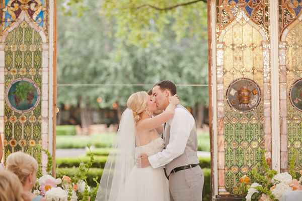 bride and groom kiss outdoors with tall stained glass windows at the alter