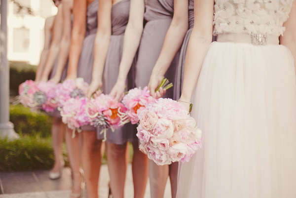 pink wedding bouquets held at the side of each bridesmaid