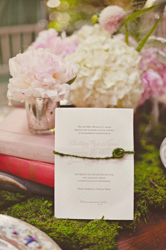 wedding invitation resting against books, pink and white flowers and a moss decorated table
