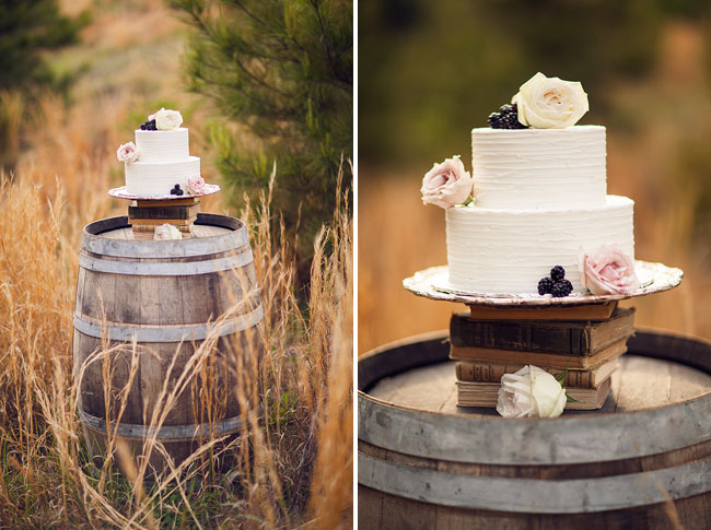 white cake with roses and blackberries on top of wine barrel