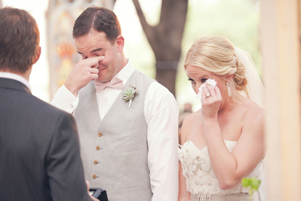 bride and groom wiping eyes during wedding ceremony
