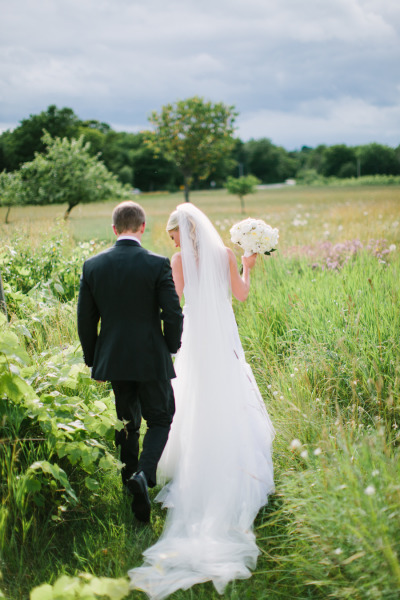 bride and groom walking into a grass field