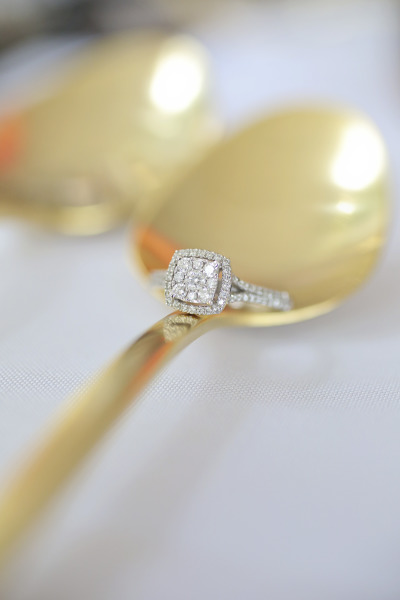 engagement ring on gold spoon
