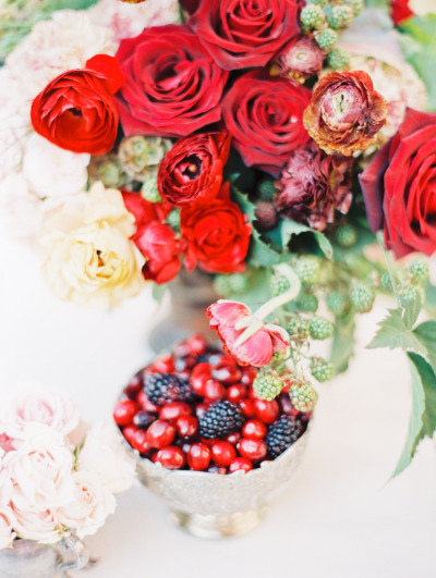 red bouquet next to light pink flowers at wedding reception with a bowl of berries