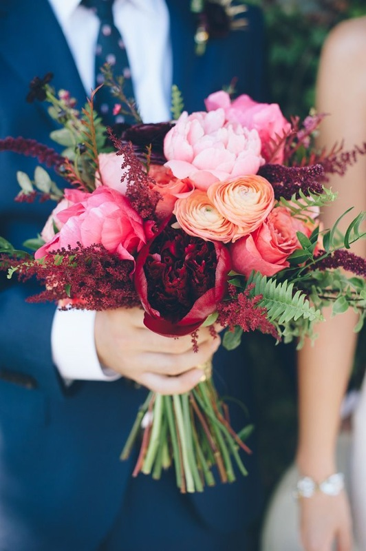 guy in navy suit holding pink and red wedding flowers