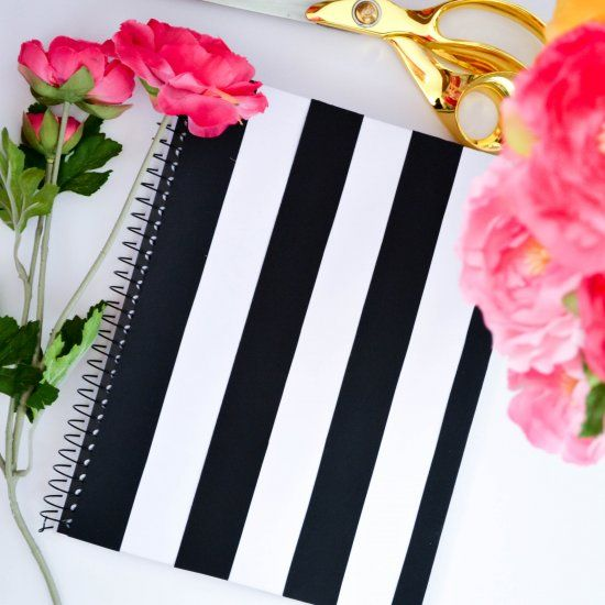 black and white striped notebook, gold scissors and pink flowers