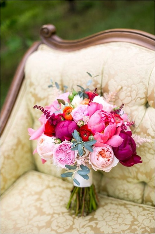 pink and red wedding bouquet on a couch