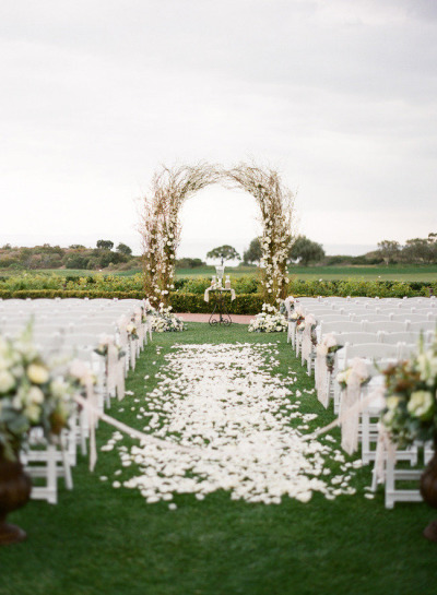 wedding alter with white chairs and arbor filled with white roses