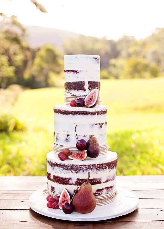 tall red velvet cake decorated with figs and grapes