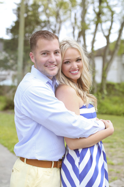 engagement photo of guy holding fiance in blue dress shirt and girl in striped blue dress