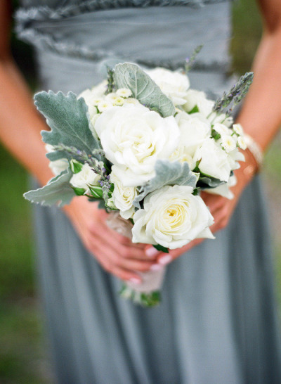 bridesmaid in silver dress holding white bouquet of roses