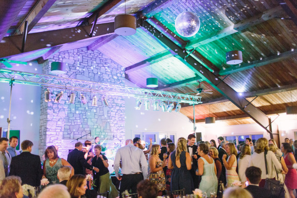 guests dancing at wedding reception with green and blue uplights