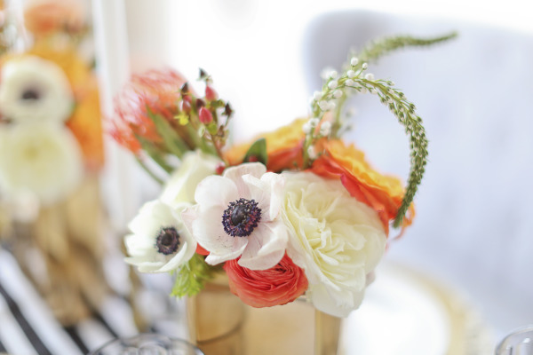 coral and white flowers in gold vases