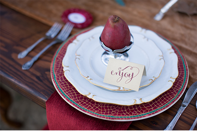 red and gold table setting with a red pear