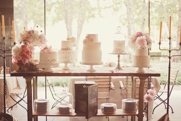 wedding cake table with 5 small white cakes with white and pink flowers