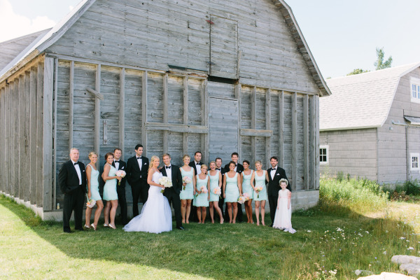 bridal party against grey barn in black tuxes and light blue bridesmaid dresses