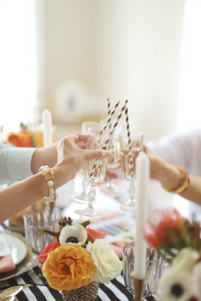 table toasting with flutes and striped straws