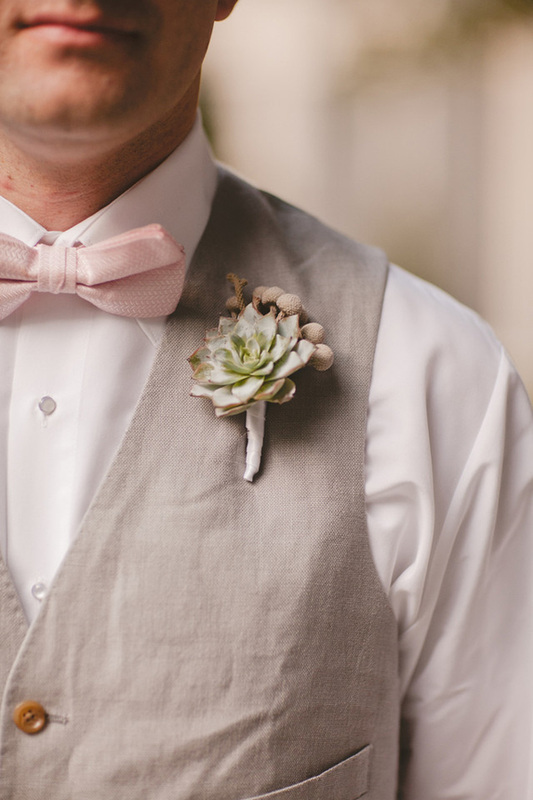 groom in grey linen suit and pink bow tie