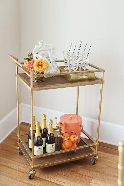gold bar cart styled with champagne, flutes, oranges, flowers and drink menu frame