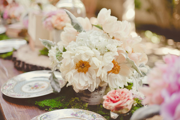 wedding reception table decorated with whit and pink flowers, moss and colorful china