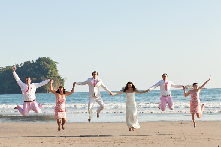 bridal party jumping in the air on a beach in pink and white wedding attire
