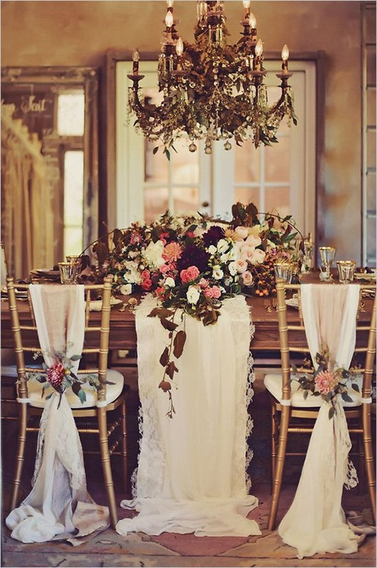 maroon, pink ad white wedding table flowers and gold chairs with white linens tied with flowers