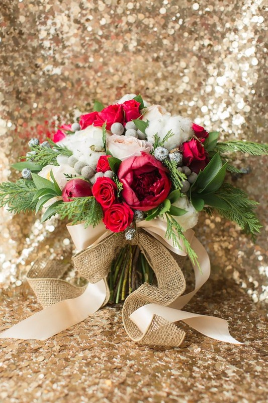 red and white wedding flowers tied with gold ribbon against gold linen