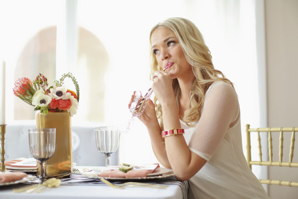 girl drinking out of striped straw at styled table