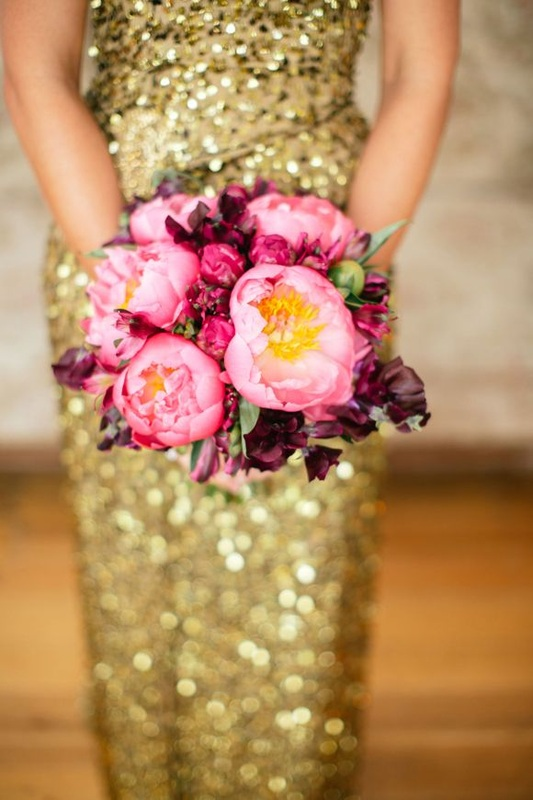 girl in gold dress holding pink and maroon bouquet