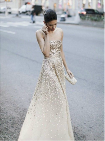 girl in NYC in glowing gown with gold sequin cascading down it