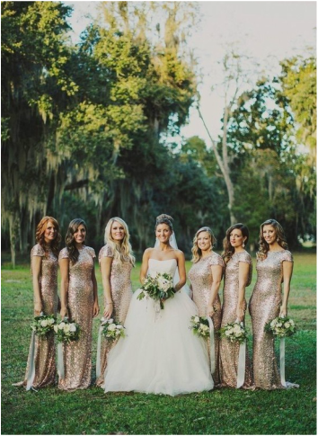 bride next to bridesmaids in long gold sequin dresses with cap sleeves