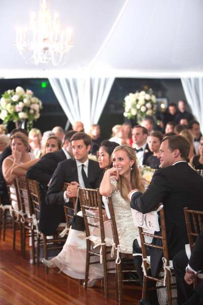 under marquee tent bride and groom listen to speeches