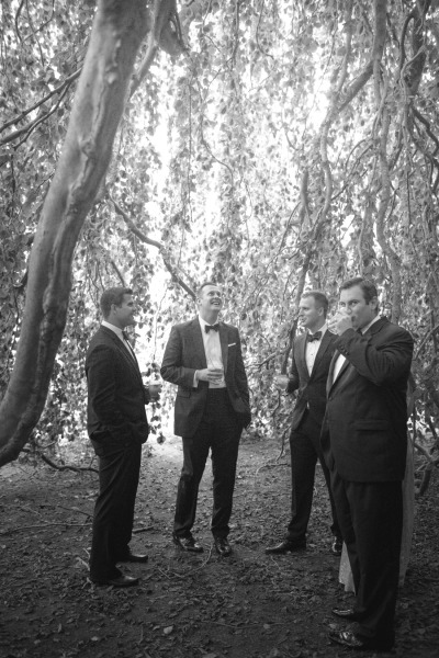 groomsmen having a drink during cocktail hour
