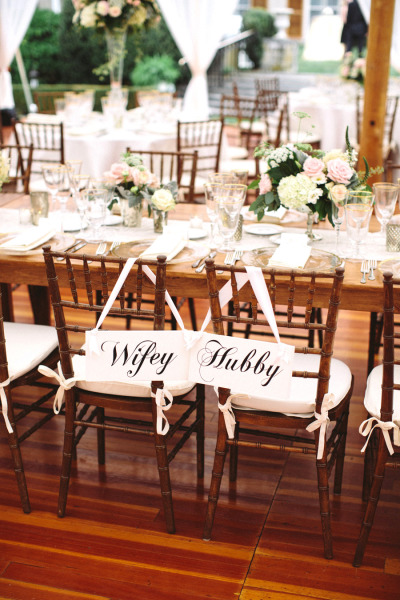 white wifey and hubby signs on the backs of chairs