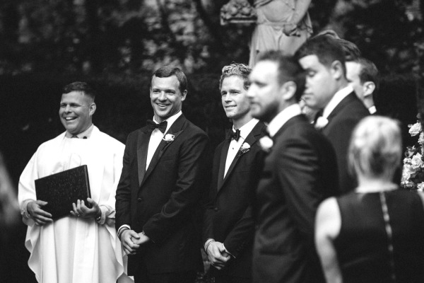 groom and groomsmen smiling in black tuxedos at ceremony alter