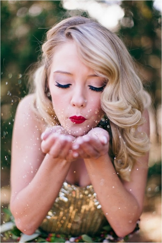 girl in shiny gold strapless dress blowing glitter