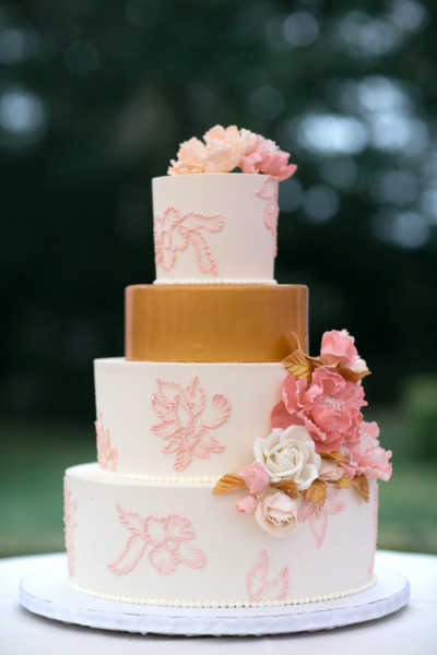 white, pink and gold wedding cake with pink flowers