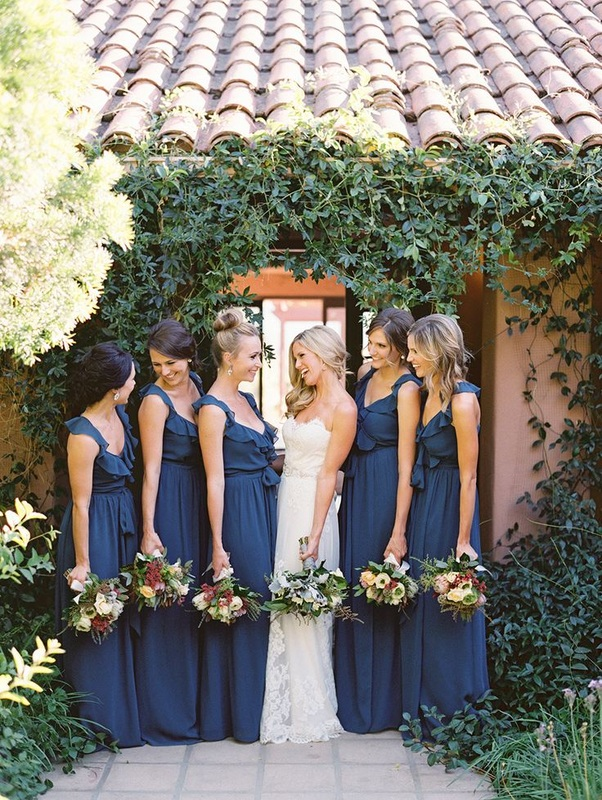 bride next to bridesmaids in navy long dresses with ruffle straps
