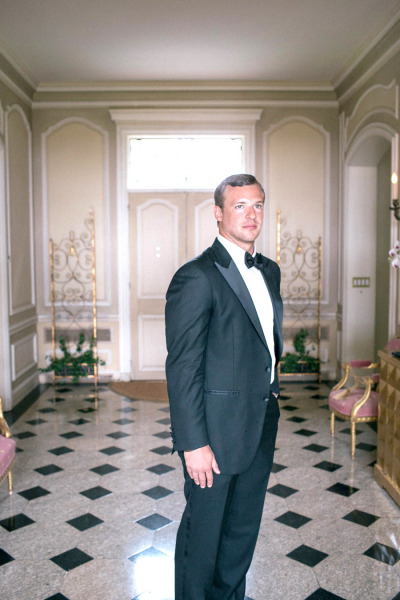 handsome groom standing in a mansion hallway