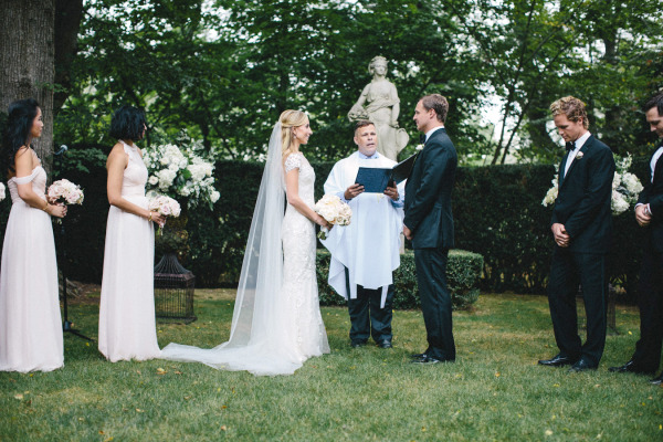 bride and groom at ceremony alter with hedges and large white bouquets