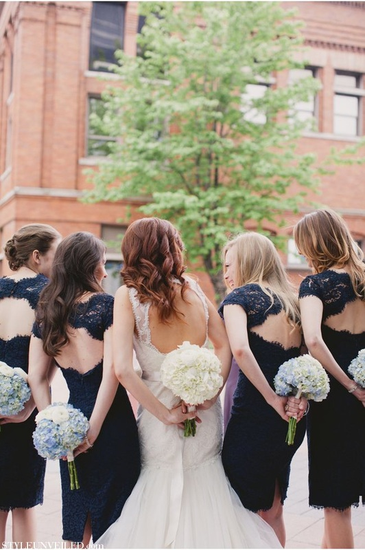 bride next to bridesmaids in navy lace dresses with keyhole back