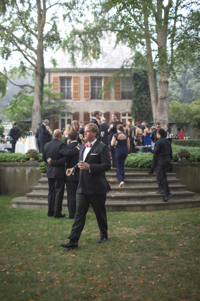 black-tie wedding cocktail hour outside with mansion in background