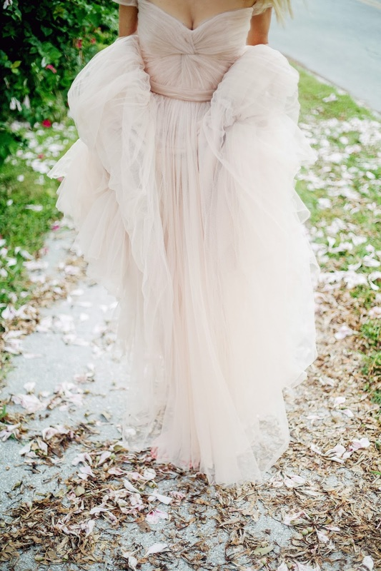 girl carrying dress with lots of tulle and sweetheart necklines and capsleeves, Reema Acra gown