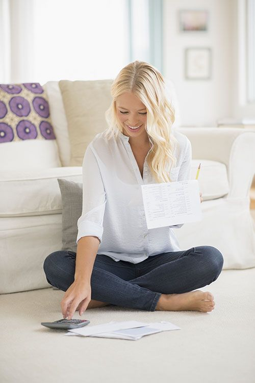 girl sitting on the floor calculating her wedding budget