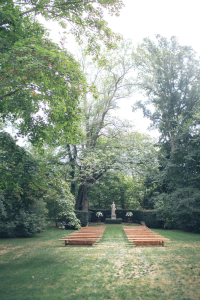 benches set up at backyard ceremony sight with hedges