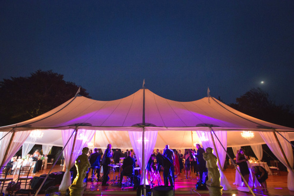 wedding marquee tent lit up with uplights and chandeliers