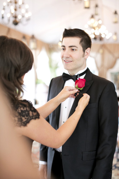 groom with red rose boutonniere