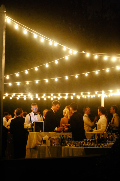 wedding cocktail hout outside with hanging edison lights