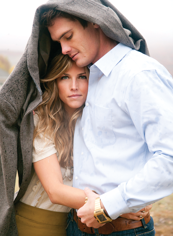 couple hug each other under a jacket in the rain